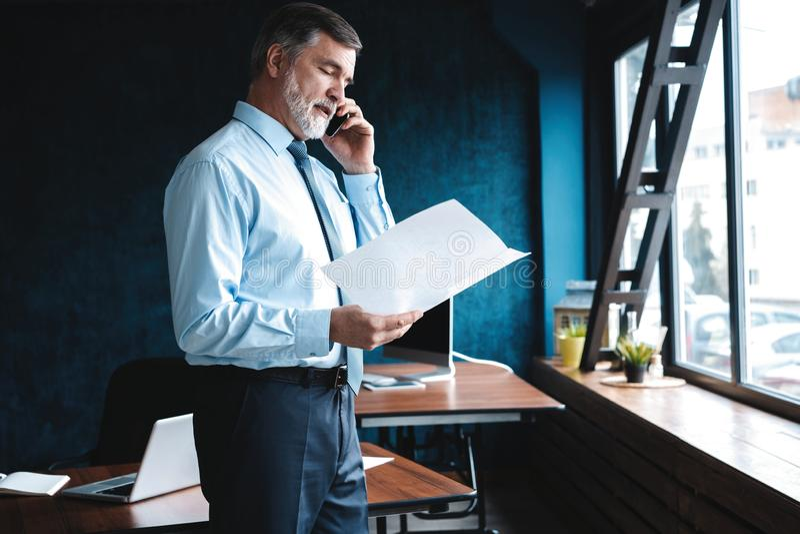 Ώριμος επιχειρηματίας που μιλά σε ένα κινητό τηλέφωνο που υπερασπίζεται το παράθυρο με την άποψη σχετικά με την πόλη στοκ εικόνες