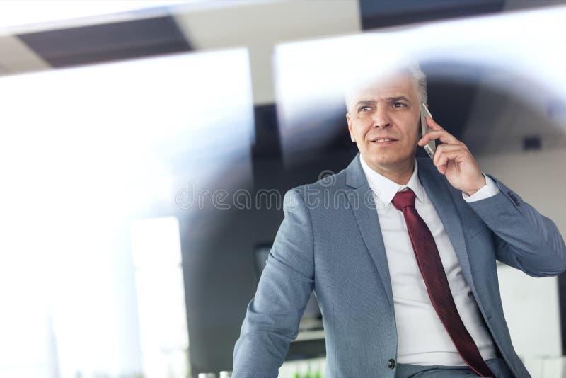 Ώριμος επιχειρηματίας που μιλά στο κινητό τηλέφωνο στο δωμάτιο πινάκων στοκ εικόνες