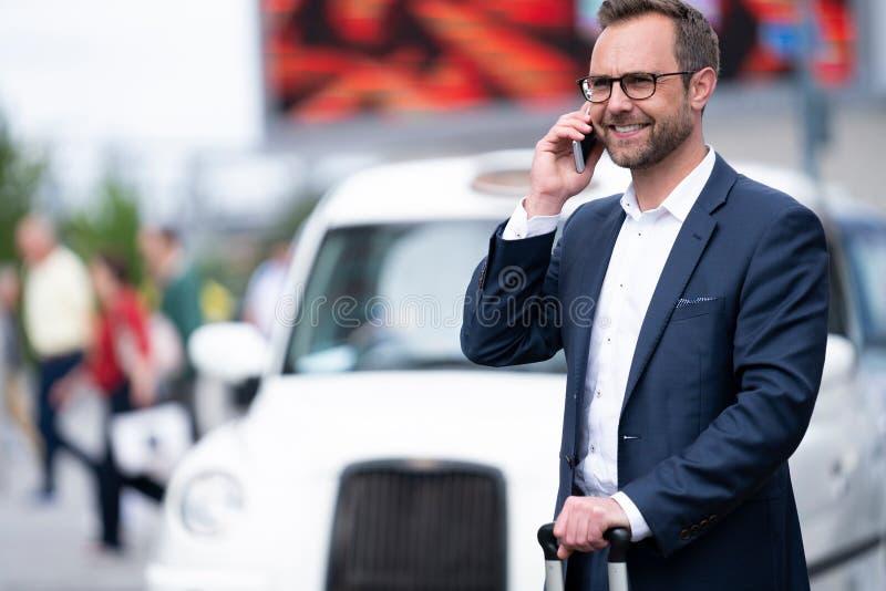 Ώριμος επιχειρηματίας που παίρνει το τηλεφώνημα στην κινητή στάση από την τάξη ταξί έξω από το σιδηροδρομικό σταθμό στοκ εικόνα με δικαίωμα ελεύθερης χρήσης