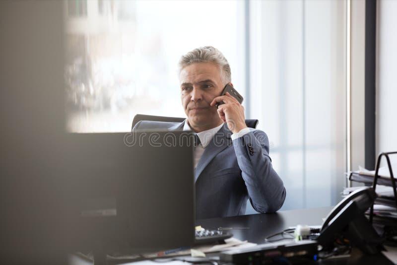 Ώριμος επιχειρηματίας που χρησιμοποιεί το κινητό τηλέφωνο στο γραφείο στην αρχή στοκ φωτογραφία με δικαίωμα ελεύθερης χρήσης
