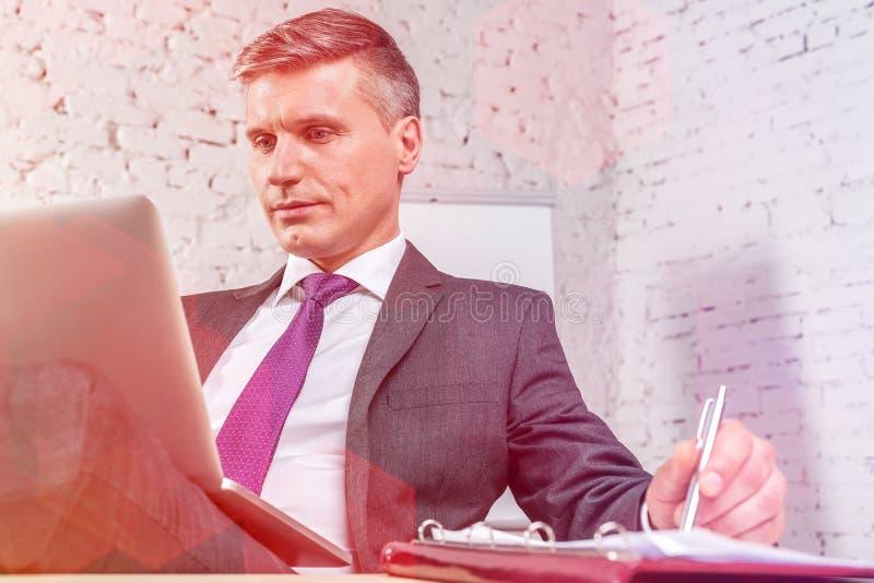 Ώριμος επιχειρηματίας που χρησιμοποιεί το lap-top στο γραφείο στοκ εικόνα με δικαίωμα ελεύθερης χρήσης