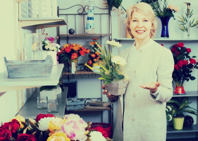 Ώριμος εύθυμος θηλυκός πελάτης που επιλέγει τα λουλούδια στοκ φωτογραφία