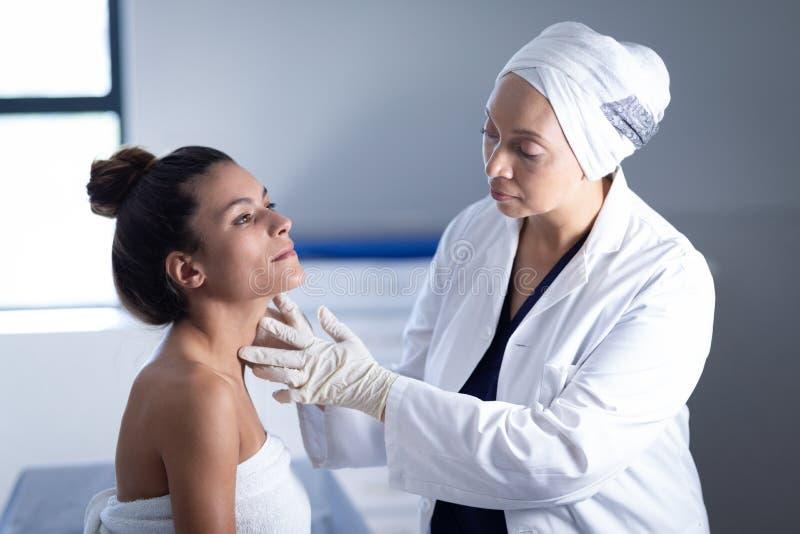 Ώριμος θηλυκός γιατρός που ελέγχει το λαιμό της γυναίκας στην κλινική στοκ εικόνες