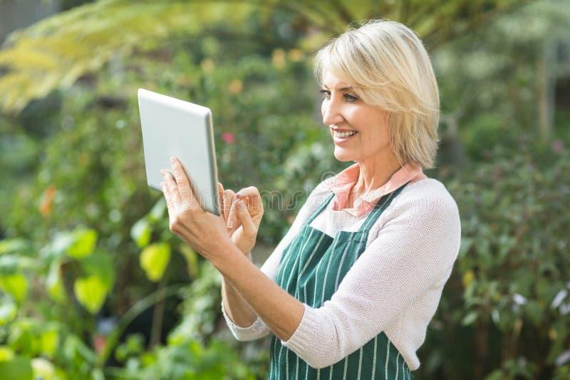 Ώριμος θηλυκός κηπουρός που χρησιμοποιεί την ψηφιακή ταμπλέτα στοκ εικόνες