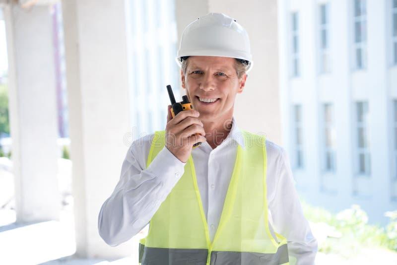 Ώριμος κατασκευαστής στον επαγγελματικό εξοπλισμό που μιλά walkie-talkie στοκ φωτογραφία με δικαίωμα ελεύθερης χρήσης