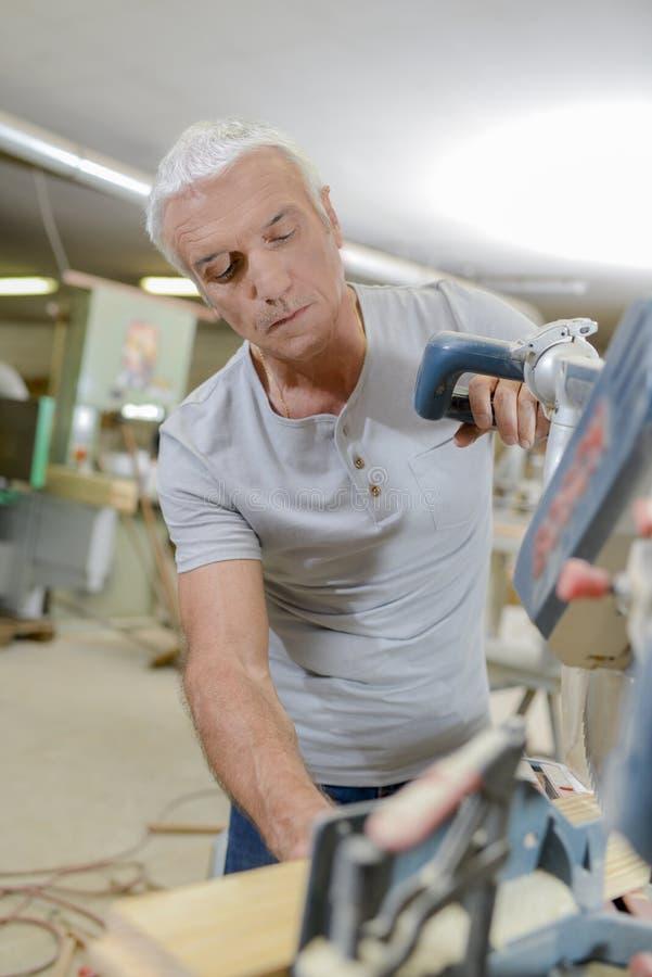 Ώριμος ξυλουργός που εργάζεται μόνο στοκ φωτογραφία
