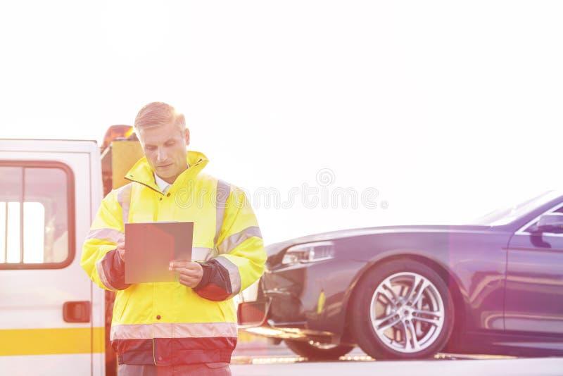 Ώριμος οδηγός φορτηγού ρυμούλκησης που κάνει τις εκθέσεις σχετικά με την περιοχή αποκομμάτων ενάντια στον ουρανό στοκ φωτογραφίες