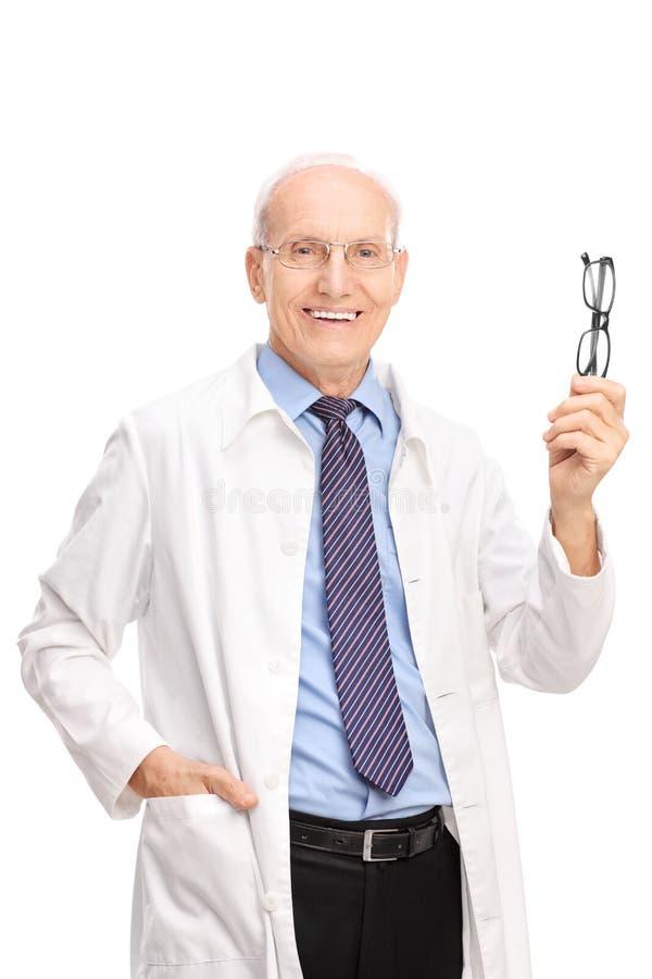 Ώριμος οπτικός που κρατά ένα ζευγάρι των γυαλιών στοκ εικόνα
