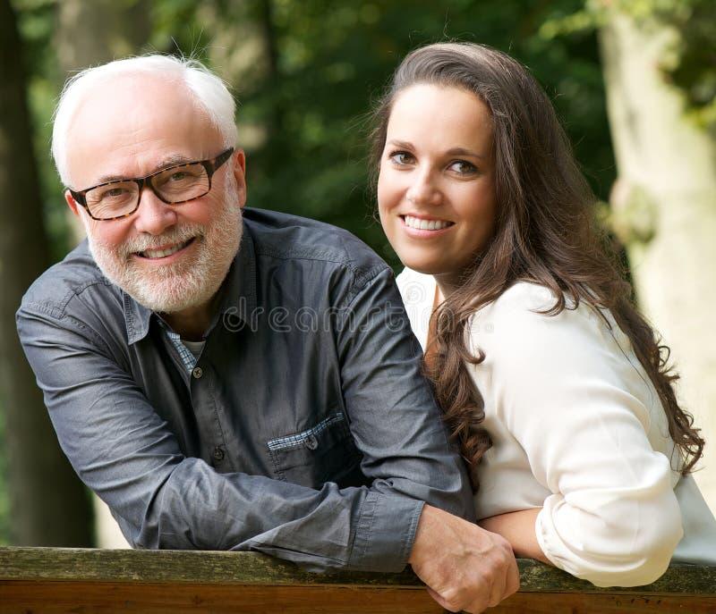 Ώριμος πατέρας και νέα κόρη που χαμογελούν υπαίθρια στοκ εικόνες