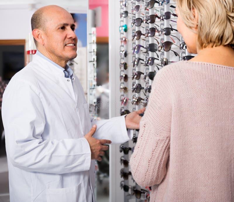 ώριμος πελάτης οπτικών ατόμων που συμβουλεύει ώριμο ξανθό κοντινό τα γυαλιά ηλίου επίδειξης στοκ φωτογραφία