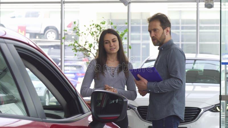 Ώριμος πωλητής που μιλά στο θηλυκό πελάτη του που προσφέρει της ένα αυτοκίνητο στοκ εικόνες