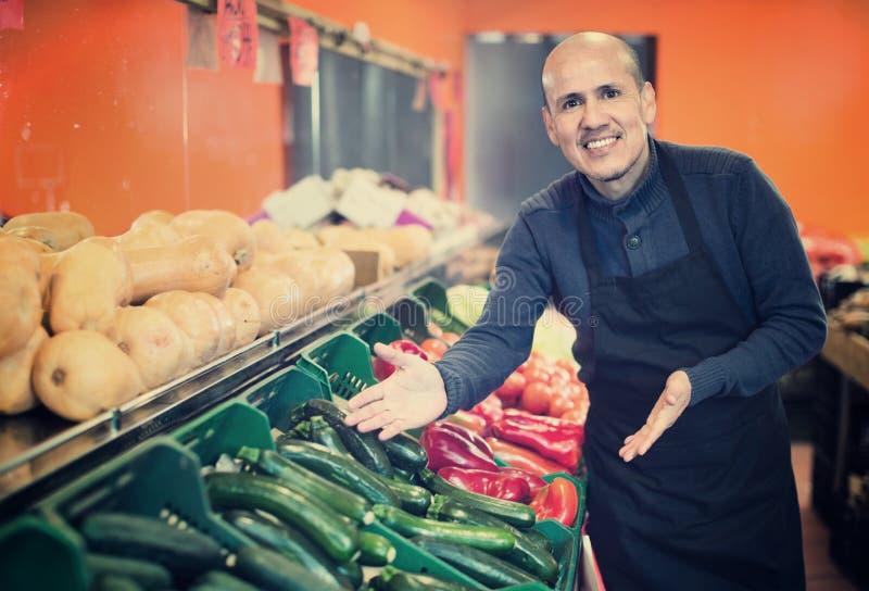 Ώριμος πωλητής που προσφέρει τα εποχιακά λαχανικά στο τοπικό παντοπωλείο στοκ φωτογραφία με δικαίωμα ελεύθερης χρήσης