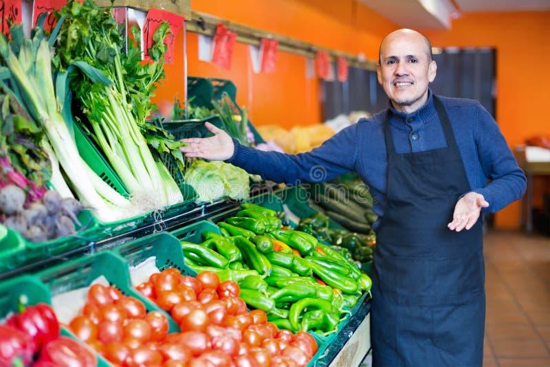 Ώριμος πωλητής που προσφέρει τα εποχιακά λαχανικά στο τοπικό παντοπωλείο στοκ εικόνα με δικαίωμα ελεύθερης χρήσης