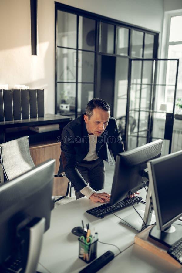 Ώριμος σκοτεινός-μαλλιαρός επιχειρηματίας που ελέγχει το ηλεκτρονικό ταχυδρομείο του στον υπολογιστή στοκ εικόνα