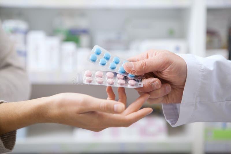 Ώριμος φαρμακοποιός που βοηθά το θηλυκό πελάτη του στοκ φωτογραφία με δικαίωμα ελεύθερης χρήσης