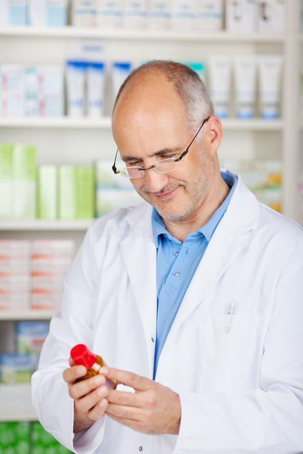 Ώριμος φαρμακοποιός που ελέγχει ένα μπουκάλι ιατρικής στοκ φωτογραφία με δικαίωμα ελεύθερης χρήσης