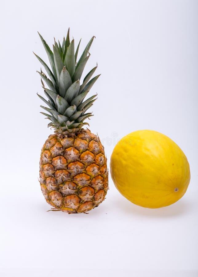 Ώριμος, φρέσκος ανανάς και κίτρινο πεπόνι που απομονώνονται στο άσπρο υπόβαθρο στοκ εικόνες