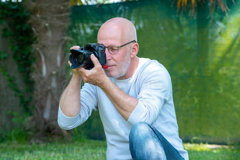 Ώριμος φωτογράφος που χρησιμοποιεί μια κάμερα στοκ φωτογραφία με δικαίωμα ελεύθερης χρήσης