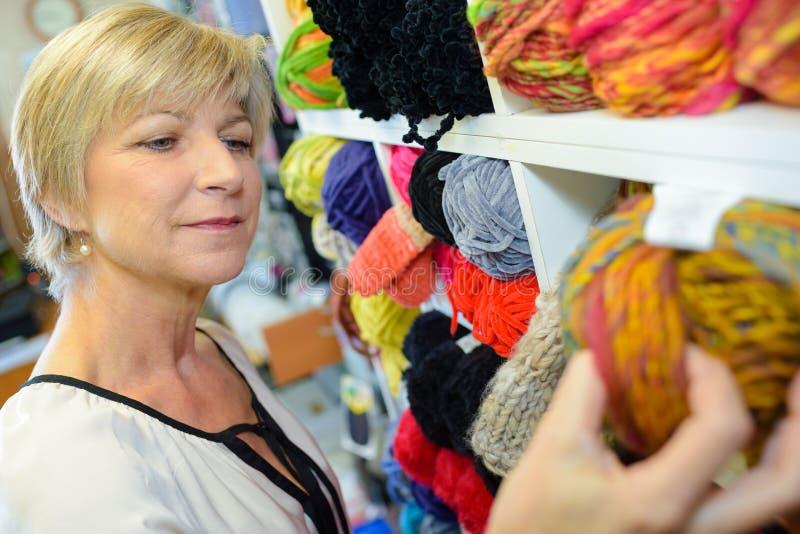 Ώριμος χαμογελώντας ξανθός πελάτης γυναικών που επιλέγει το πολύχρωμο στροφίο με το νήμα στοκ εικόνα με δικαίωμα ελεύθερης χρήσης