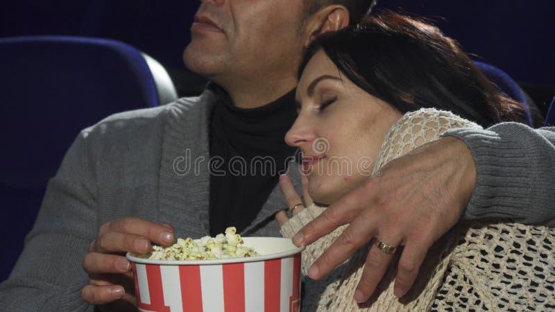 Ώριμος ύπνος γυναικών στον ώμο του συζύγου της στον κινηματογράφο στοκ εικόνα με δικαίωμα ελεύθερης χρήσης