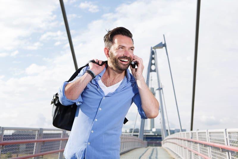 Ώριμο άτομο με την τσάντα που μιλά στο κινητό τηλέφωνο και το γέλιο στοκ φωτογραφίες με δικαίωμα ελεύθερης χρήσης