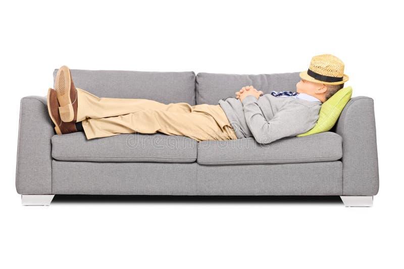 Ώριμο άτομο με το καπέλο πέρα από τον επικεφαλής ύπνο του σε έναν καναπέ στοκ εικόνα με δικαίωμα ελεύθερης χρήσης