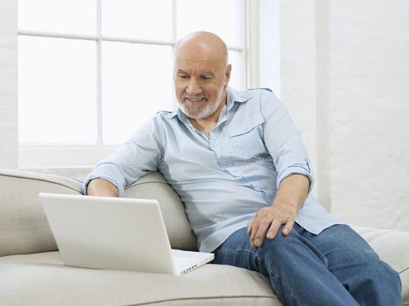Ώριμο άτομο με το lap-top στον καναπέ στοκ φωτογραφία