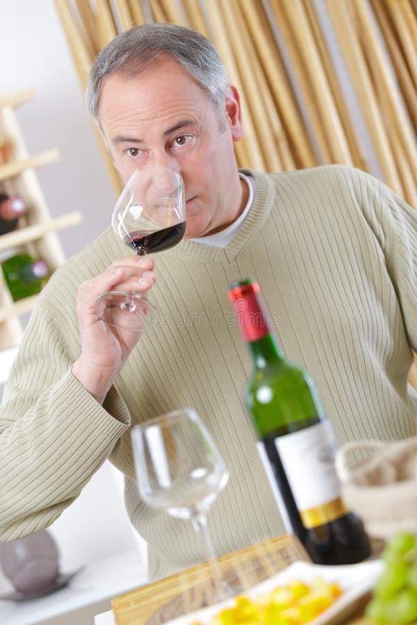 Ώριμο άτομο που απολαμβάνει το κόκκινο κρασί γυαλιού στοκ φωτογραφία