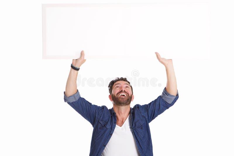 Ώριμο άτομο που γελά και που κρατά το κενό σημάδι αφισών στοκ εικόνα με δικαίωμα ελεύθερης χρήσης