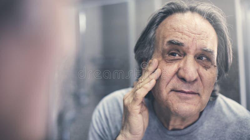 Ώριμο άτομο που ελέγχει τις ρυτίδες του στοκ εικόνες