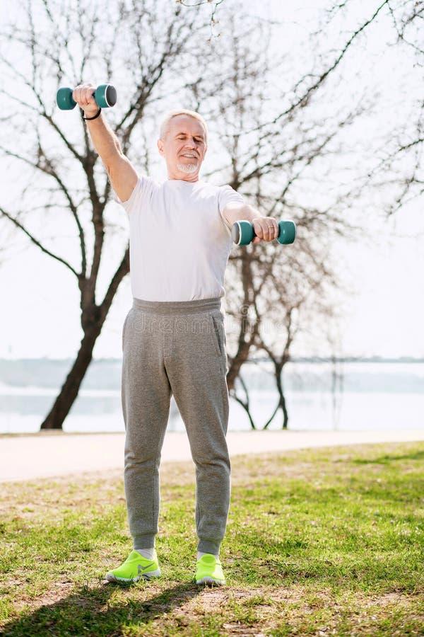 Ώριμο άτομο που ενισχύει τους μυς στοκ φωτογραφίες