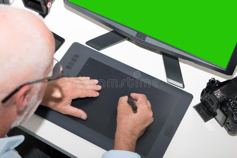 Ώριμο άτομο που εργάζεται με την ταμπλέτα γραφικής παράστασης στην αρχή στοκ εικόνες