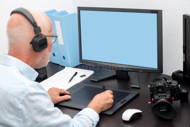 Ώριμο άτομο που εργάζεται με την ταμπλέτα γραφικής παράστασης στο γραφείο του στοκ φωτογραφίες με δικαίωμα ελεύθερης χρήσης