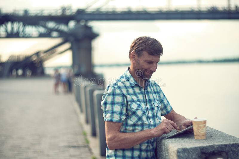 Ώριμο άτομο που κοιτάζει βιαστικά στην ψηφιακή ταμπλέτα το καλοκαίρι, στην αποβάθρα ποταμών στοκ φωτογραφίες