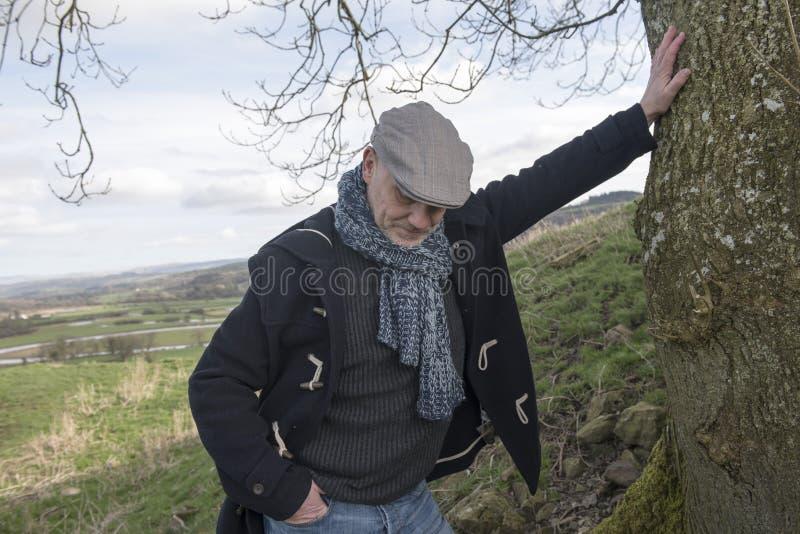 Ώριμο άτομο που κοιτάζει κάτω στο έδαφος στοκ εικόνες