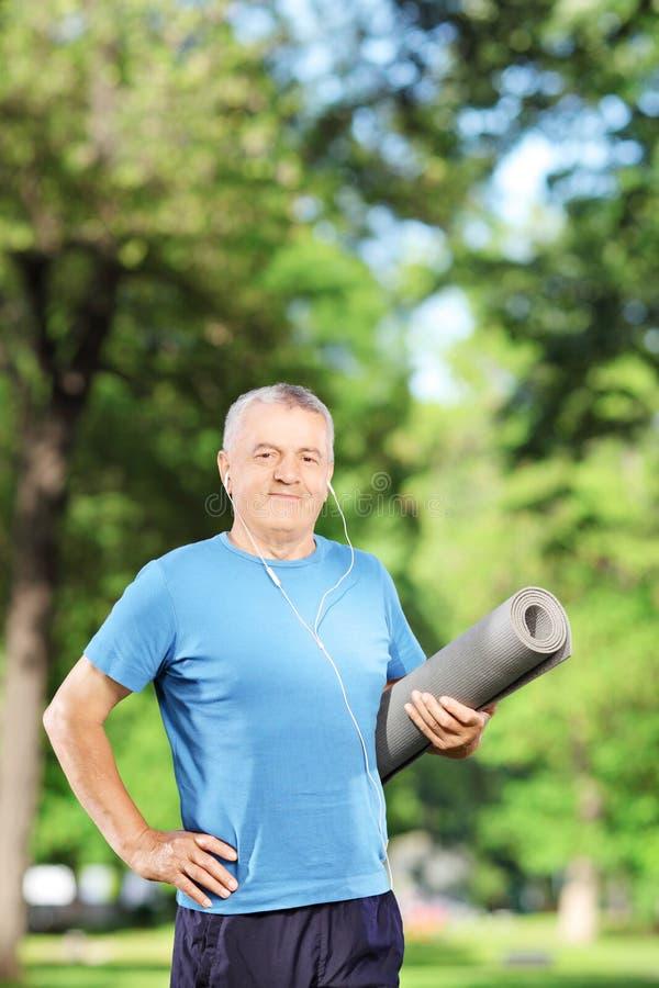 Ώριμο άτομο που κρατά ένα ασκώντας χαλί στο πάρκο στοκ φωτογραφία με δικαίωμα ελεύθερης χρήσης