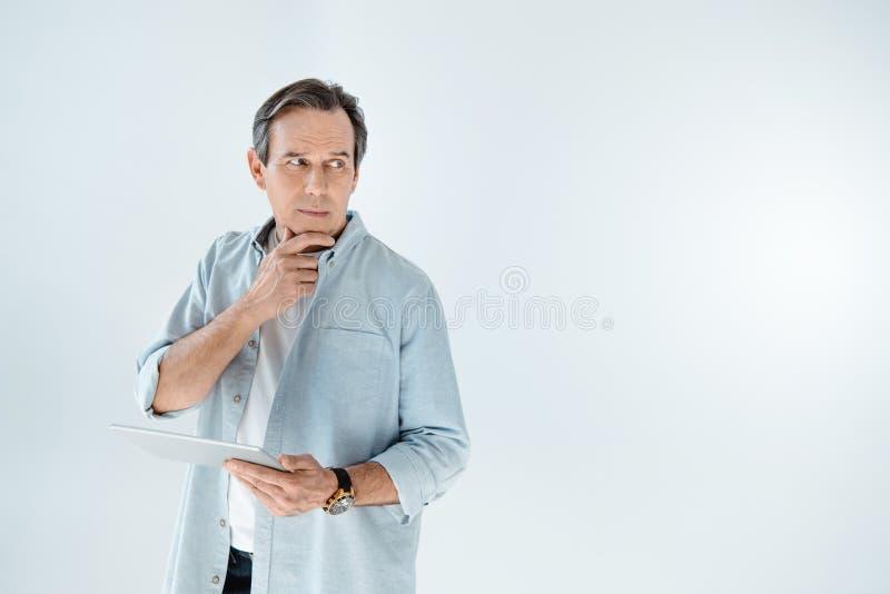 Ώριμο άτομο που κρατά την ψηφιακή ταμπλέτα και που κοιτάζει μακριά στο γκρι στοκ φωτογραφίες με δικαίωμα ελεύθερης χρήσης