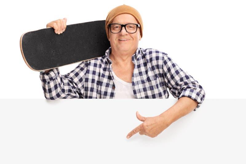 Ώριμο άτομο που κρατά skateboard πίσω από μια επιτροπή στοκ φωτογραφίες