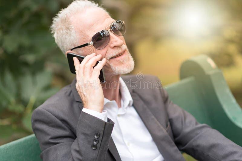 Ώριμο άτομο που μιλά στο κινητό τηλέφωνο, ελαφριά επίδραση στοκ εικόνα με δικαίωμα ελεύθερης χρήσης