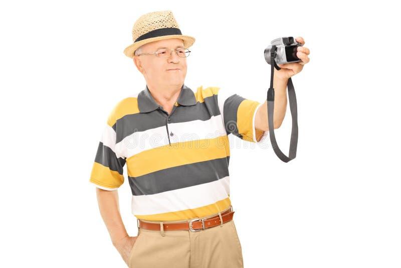 Ώριμο άτομο που παίρνει την εικόνα του με τη κάμερα στοκ φωτογραφίες