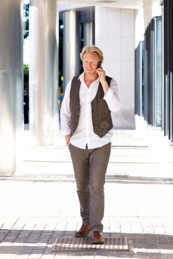 Ώριμο άτομο που περπατά γύρω από την πόλη και που μιλά στο κινητό τηλέφωνο στοκ εικόνα με δικαίωμα ελεύθερης χρήσης