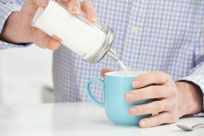 Ώριμο άτομο που προσθέτει τη ζάχαρη στο φλιτζάνι του καφέ στοκ εικόνες