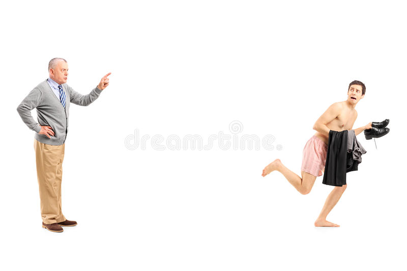 Ώριμο άτομο που φωνάζει σε ένα νέο γυμνό άτομο που τρέχει μακριά στοκ φωτογραφία