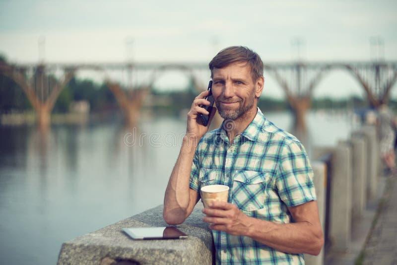 Ώριμο άτομο στην αποβάθρα ποταμών που μιλά στο κινητό τηλέφωνο στοκ φωτογραφία