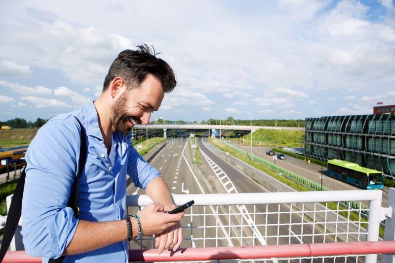 Ώριμο άτομο στη γέφυρα που χρησιμοποιεί το κινητό τηλέφωνο στοκ εικόνα