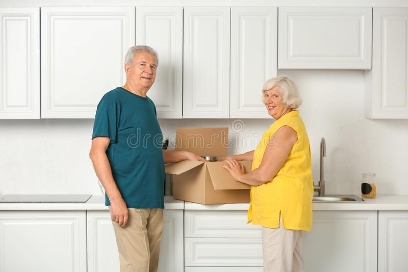 Ώριμο ανοίγοντας κινούμενο κιβώτιο ζευγών με τις περιουσίες στην κουζίνα στοκ εικόνα με δικαίωμα ελεύθερης χρήσης