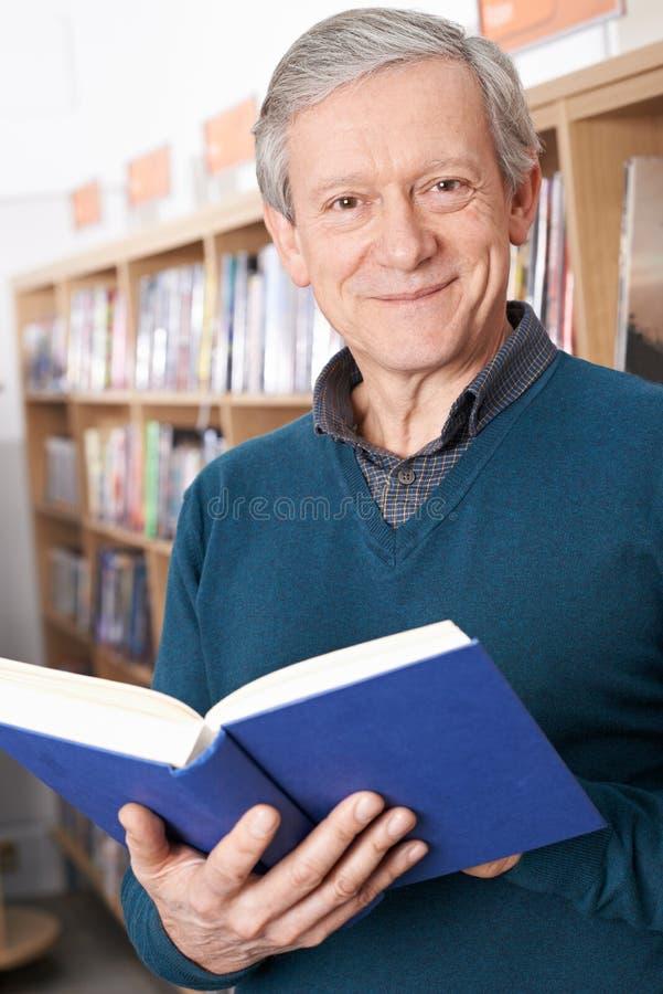 Ώριμο βιβλίο ανάγνωσης ανδρών σπουδαστών στη βιβλιοθήκη στοκ φωτογραφίες