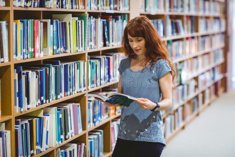 Ώριμο βιβλίο ανάγνωσης σπουδαστών στη βιβλιοθήκη που φορά το έξυπνο ρολόι στοκ εικόνα με δικαίωμα ελεύθερης χρήσης
