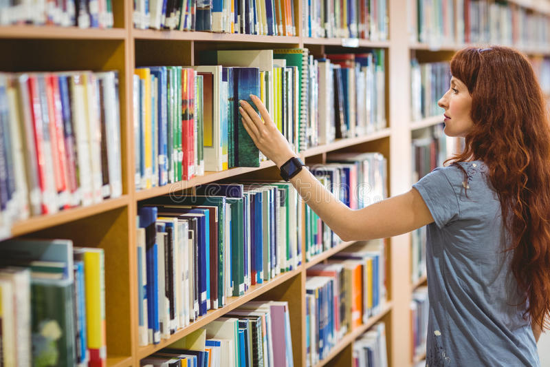 Ώριμο βιβλίο επιλογής σπουδαστών στη βιβλιοθήκη που φορά το έξυπνο ρολόι στοκ φωτογραφίες