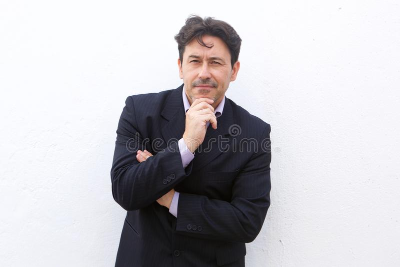 Ώριμο επιχειρησιακό άτομο που σκέφτεται με ένα χέρι στο πηγούνι στο άσπρο υπόβαθρο στοκ εικόνα με δικαίωμα ελεύθερης χρήσης